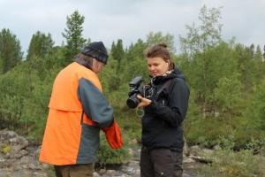 Stiina Aikio dokumentoi ennallistamistyötä ja kerää tässä Vladimir Feodoroffilta kolttasaamelaista perinnetietoa osana työtä.